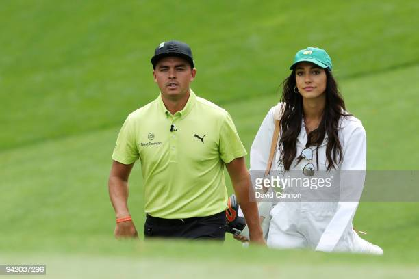 Rickie Fowler of the United States walks with girlfriend Allison Stokke during the Par 3 Contest prior to the start of the 2018 Masters Tournament at...