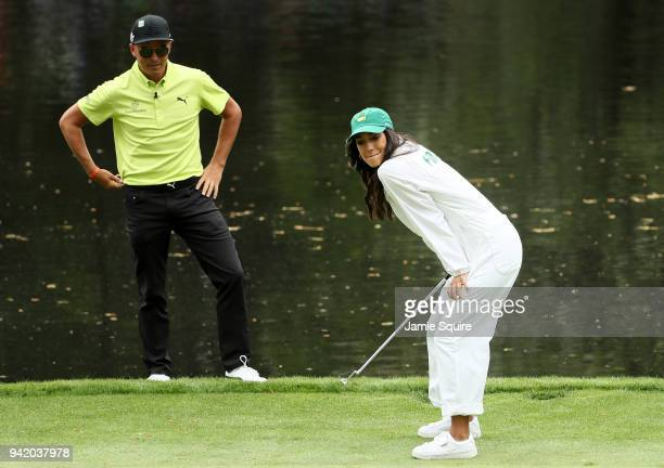 Rickie Fowler of the United States watches his girlfriend Allison Stokke during the Par 3 Contest prior to the start of the 2018 Masters Tournament...