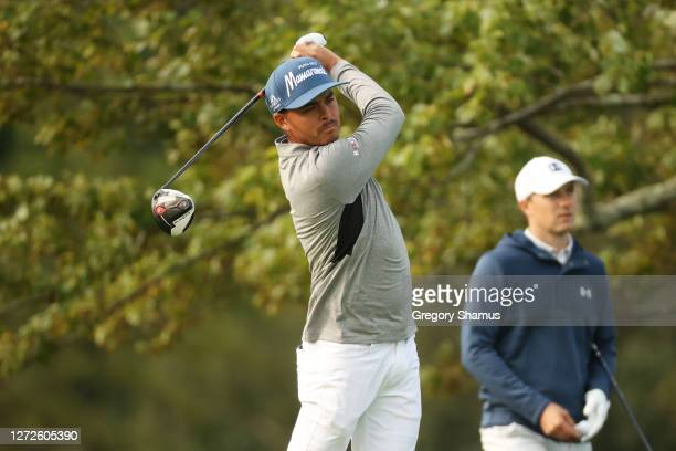 Rickie Fowler of the United Statesplays his shot from the second tee as Jordan Spieth of the United States looks on during a practice round prior to...