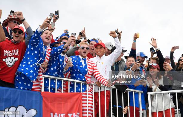 Rickie Fowler of the US Team cheers in the stands with US Team fans during the afternoon fourball matches at the Presidents Cup at Liberty National...