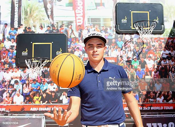 Rickie Fowler of the USA is pictured with a basketball during his visit to the tented village following his first round of the Abu Dhabi HSBC Golf...