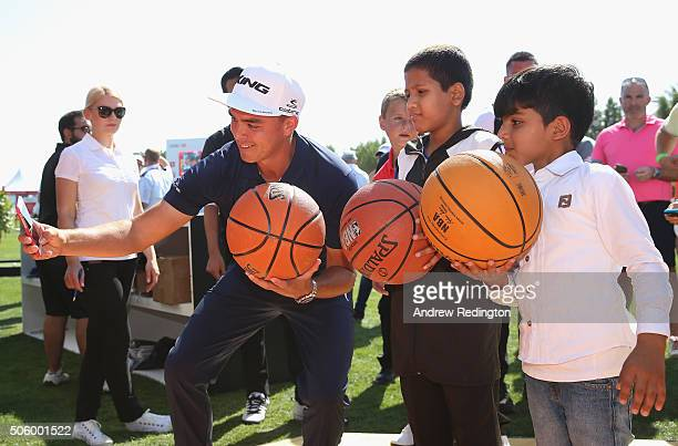 Rickie Fowler of the USA takes a selfie with some schoolchildren during his visit to the tented village following his first round of the Abu Dhabi...