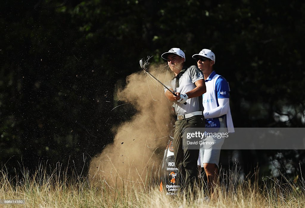 Rickie Fowler plays a shot alongside his caddie Joe Skovron on the 13th hole during the third round of The Barclays in the PGA Tour FedExCup Play-Offs on the Black Course at Bethpage State Park on August 27, 2016 in Farmingdale, New York.