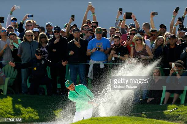 Rickie Fowler plays a shot from a bunker on the 18th hole during the third round of the Waste Management Phoenix Open at TPC Scottsdale on February...