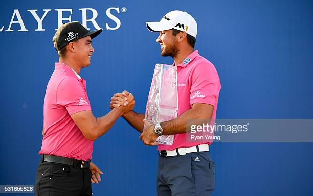 Rickie Fowler presents the trophy to Jason Day of Australia during the final round of THE PLAYERS Championship on THE PLAYERS Stadium Course at TPC...
