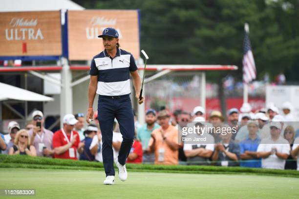 Rickie Fowler raises his putter to fans on the twelfth hole after making a putt during the second round of the Rocket Mortgage Classic at Detroit...