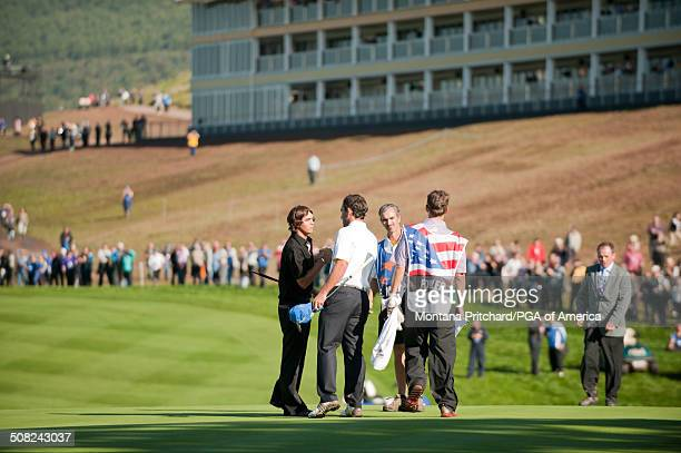 Rickie Fowler shakes hands with Edoardo Molinari on the eighteenth hole during the session four singles matches at the 38th Ryder Cup at the Twenty...