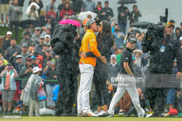 Rickie Fowler shares a kiss in the pouring rain with his fiancé' Allison Stokke after winning the Waste Management Phoenix Open at TPC Scottsdale on...
