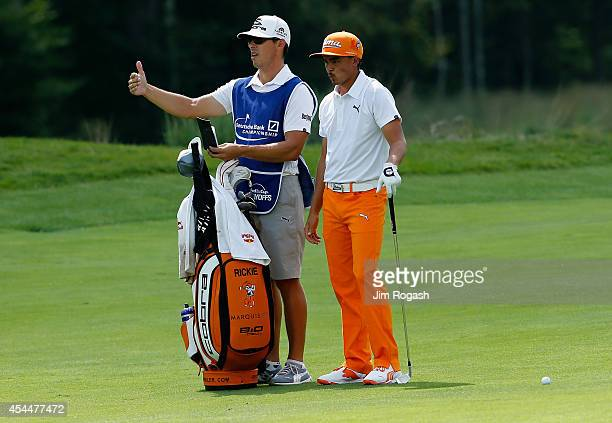 Rickie Fowler talks with his caddie on the second hole during the final round of the Deutsche Bank Championship at the TPC Boston on September 1 2014...