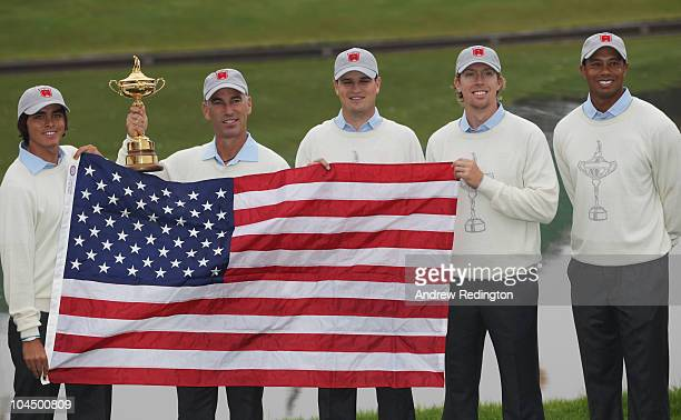 Rickie Fowler Team Captain Corey Pavin Zach Johnson Hunter Mahan and Tiger Woods pose with the trophy and the American flag during the USA Team...