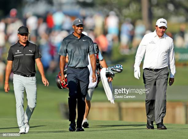 Rickie Fowler, Tiger Woods and Phil Mickelson of the United States walk to their second shots on the par 4, 10th hole during the second round of the...