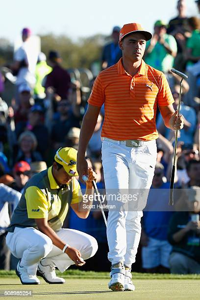 Rickie Fowler walks in front of Hideki Matsuyama of Japan on the third playoff hole during the final round of the Waste Management Phoenix Open at...