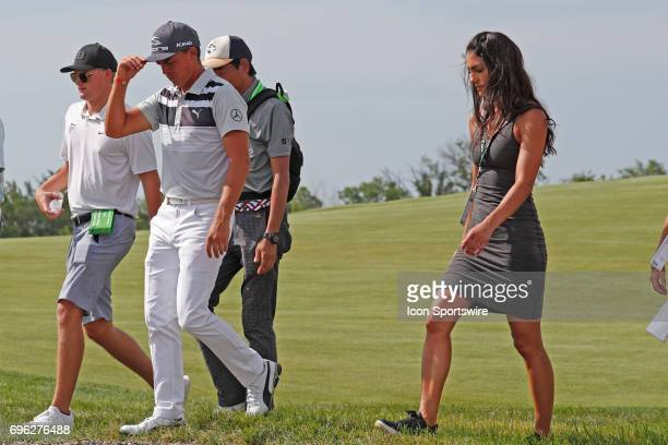 Rickie Fowler walks to the 9th tee with his girlfriend during a practice round for the 117th US Open at Erin Hills in Erin Wisconsin