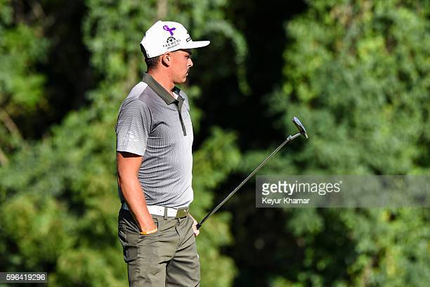 Rickie Fowler, wearing a purple ribbon in support of Baton Rouge flooding victims, watches his putt on the 15th hole green during the third round of...