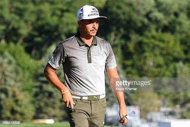Rickie Fowler, wearing a purple ribbon in support of Baton Rouge flooding victims, walks off the 15th hole green during the third round of The...