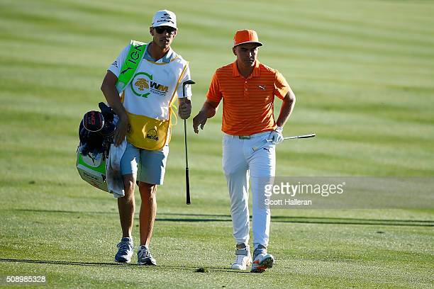 Rickie Fowler with his caddie Joe Skovron walk up the 18th hole during the final round of the Waste Management Phoenix Open at TPC Scottsdale on...