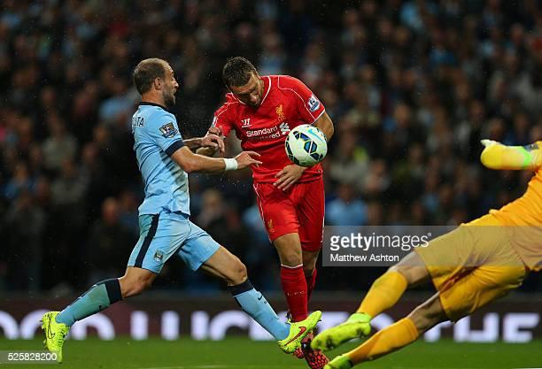 Rickie Lambert of Liverpool heads the ball towards goalkeeper Joe Hart of Manchester City who clears but Pablo Zabaleta of Manchester City...