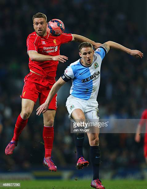 Rickie Lambert of Liverpool jumps with Matthew Kilgallon of Blackburn Rovers during the FA Cup Quarter Final Replay match between Blackburn Rovers...