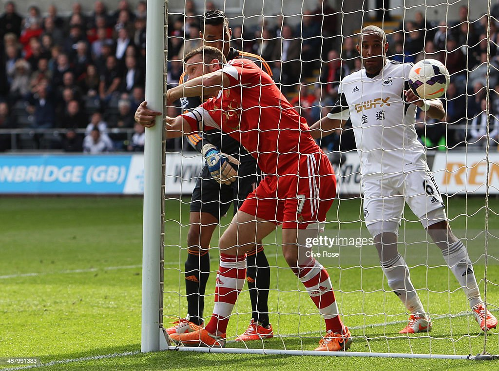 Rickie Lambert of Southampton beats Michel Vorm and Ashley Williams of Swansea City to score their first goal during the Barclays Premier League match between Swansea City and Southampton at Liberty Stadium on May 3, 2014 in Swansea, Wales.