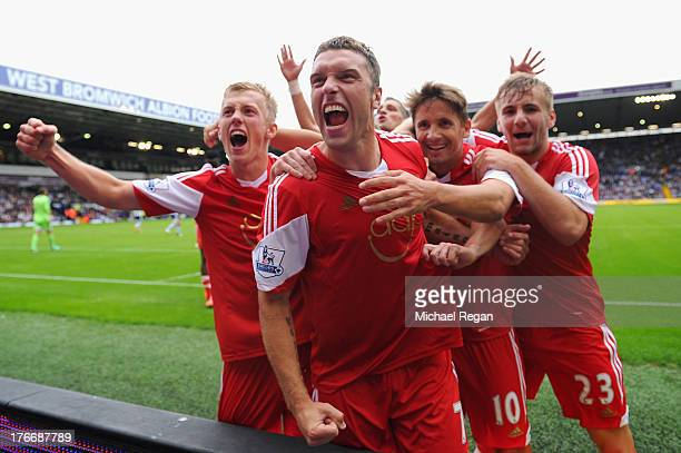 Rickie Lambert of Southampton celebrates scoring the winning goal with team mates during the Barclays Premier League match between West Bromwich...