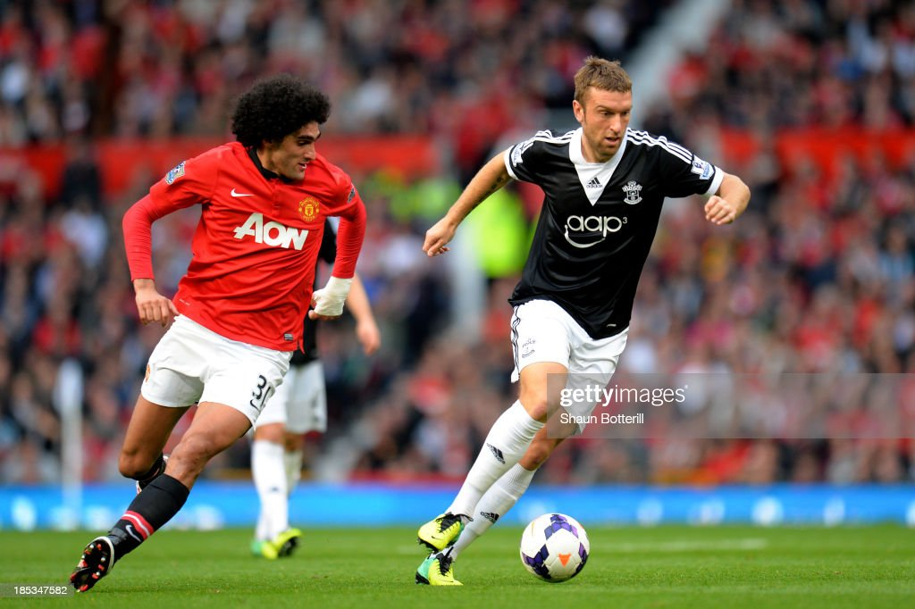 Rickie Lambert of Southampton is pursued by Marouane Fellaini of Manchester United during the Barclays Premier League match between Manchester United and Southampton at Old Trafford on October 19, 2013 in Manchester, England.
