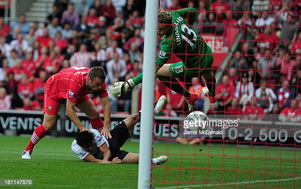 Rickie Lambert of Southampton scores a goal despite the challenge of Rafael of Manchester United during the Barclays Premier League match between...