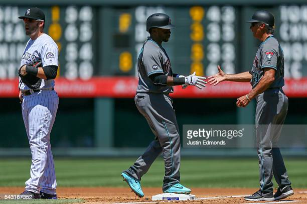 Rickie Weeks of the Arizona Diamondbacks gets a handshake from first base coach Dave McKay after hitting an RBI single during the first inning as...
