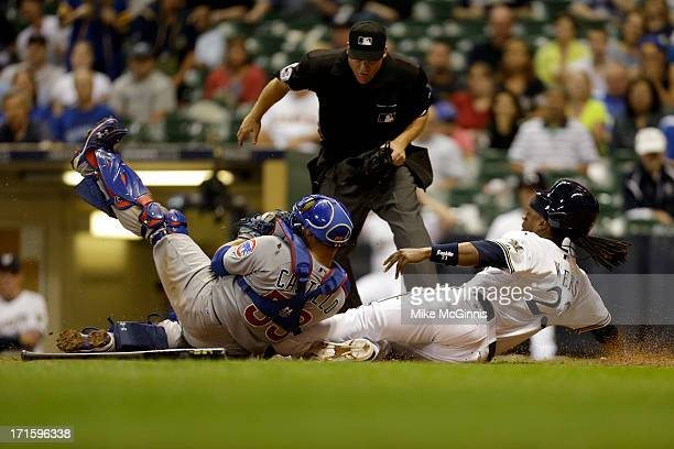 Rickie Weeks of the Milwaukee Brewers gets tagged out at home plate by Wellington Castillo of the Chicago Cubs during the bottom of the ninth inning...