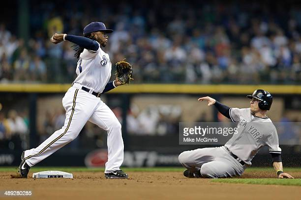Rickie Weeks of the Milwaukee Brewers turns the double play as Brendan Ryan of the New York Yankees slides into second base in the top of the third...