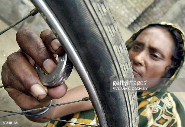 Rickshaw and bicycle repair person Begum Ayesha fixed the spokes of a rickshaw along a busy street in Dhaka 10 March 2005 Ayesha supports a family of...