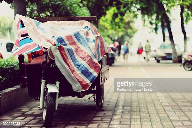 rickshaw covered in plastic parked on sidewalk - parham emrouz stock pictures, royalty-free photos & images