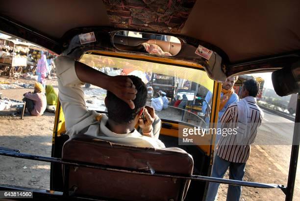 A rickshaw driver talks over the phone at Jhodage village in Nashik distict on Mumbai Agra Natioan Highway No 3 on January 21 2010 in Mumbai India