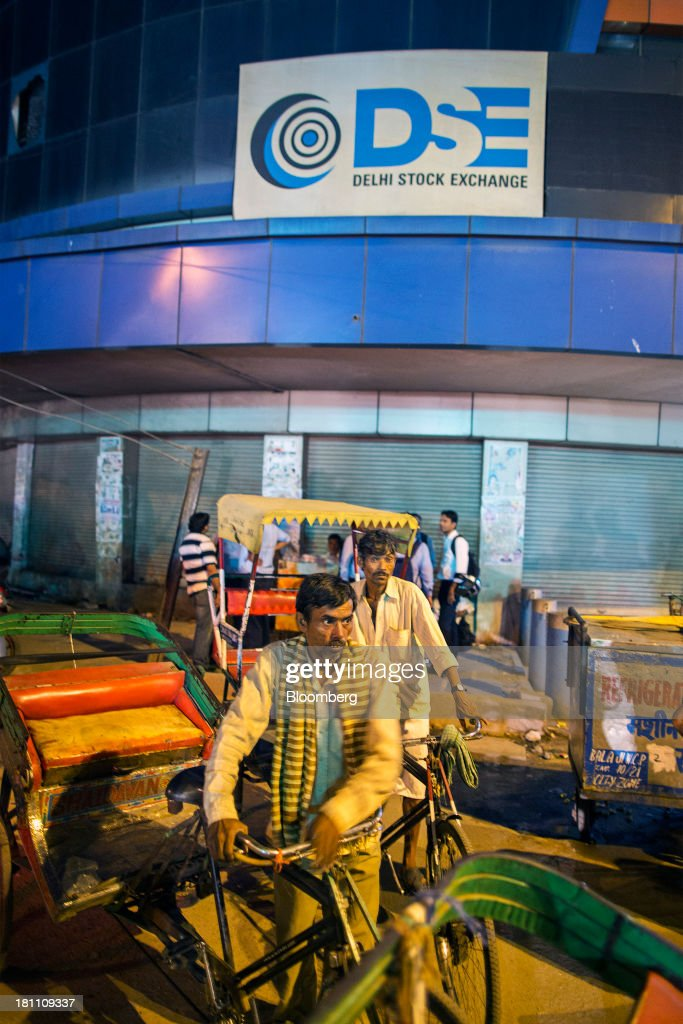Rickshaw drivers pass in front of the Delhi Stock Exchange Ltd. building in New Delhi, India, on Wednesday, Sept. 18, 2013. The Federal Reserves decision to postpone its rollback of U.S. stimulus offered Asian policy makers extra time to address domestic economic fragilities as the region copes with diminished capital inflows. Photographer: Prashanth Vishwanathan/Bloomberg via Getty Images