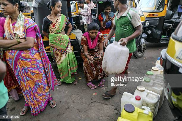 Rickshaw drivers stand by as people wait in line to fill water cans from a public outlet outside Mumbra railway station in Mumbai India on Sunday...