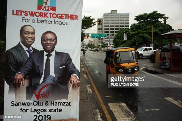 Rickshaw drives past a campaign poster of gubernatorial candidate of the ruling All Progressives Congress party in Lagos, Babajide Sanwo-Olu , and...