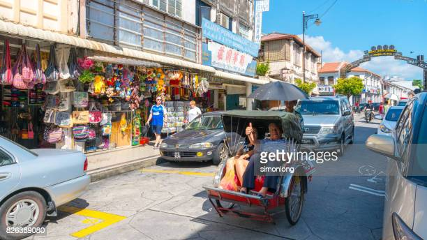 a rickshaw on the road in penang, malaysia. - rickshaw stock photos and pictures