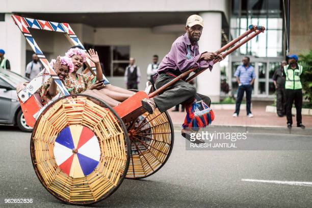 A rickshaw puller gestures as hundreds of people dressed in traditional attire in Durban take part on May 26 2018 in a street carnival festival...