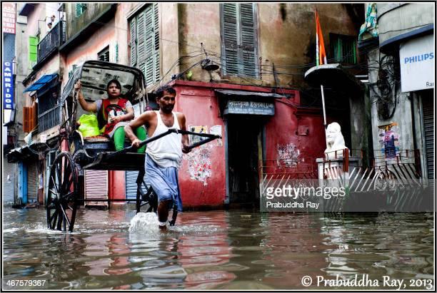 CONTENT] A rickshaw puller in the waterlogged street of kolkata