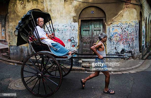 CONTENT] A rickshaw puller is carrying an old man in his hand pulled rickshaw in the lanes of north Kolkata