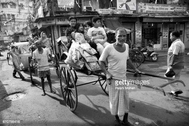 A rickshaw puller pulling his rickshaw loaded with passengers through the small lane ways September 22 2010 in Kolkata India Kolkata has...