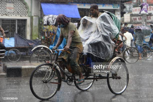 Rickshaw puller rides passengers on a street during heavy rainfall in Dhaka. Dhaka is getting back to its normal life after months of the ongoing...