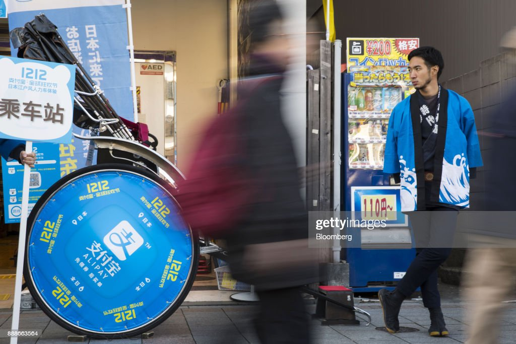 A rickshaw puller, right, waits for customers during a campaign event for Ant Financial Services Group's Alipay, an affiliate of Alibaba Group Holding Ltd., in Tokyo, Japan, on Saturday, Dec. 9, 2017. Ant Financial and its strategic partners outside China should be able to nearly double users of their payments systems in coming years, Ant's overseas operations president Douglas Feagin said on Nov. 14. Photographer: Shiho Fukada/Bloomberg via Getty Images