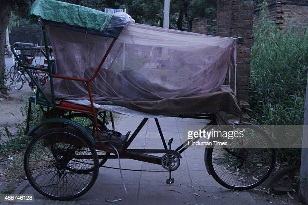 A rickshaw puller sleeps while covering himself under mosquito net amid dengue outbreak on September 17 2015 in New Delhi India Delhi remained in the...