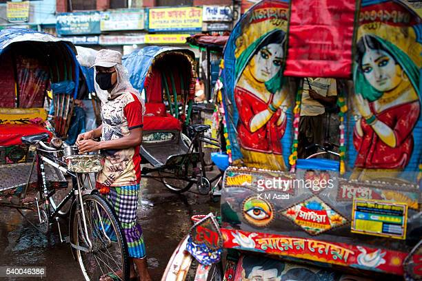 OLD DHAKA DHAKA BANGLADESH A rickshaw puller stands in the street during a rainy day the first day of Ramadan in old Dhaka Bangladesh June 07 2016...