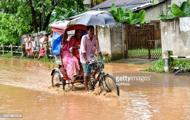 Rickshaw puller transport customers through floodwaters in the Anilnagar area of Guwahati, Assam, India on Monday, July 30, 2018.