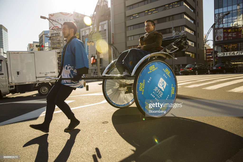 A rickshaw puller transports a customer during a campaign event for Ant Financial Services Group's Alipay, an affiliate of Alibaba Group Holding Ltd., in Tokyo, Japan, on Saturday, Dec. 9, 2017. Ant Financial and its strategic partners outside China should be able to nearly double users of their payments systems in coming years, Ant's overseas operations president Douglas Feagin said on Nov. 14. Photographer: Shiho Fukada/Bloomberg via Getty Images