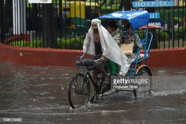 A rickshaw puller transports passengers during rainfall at Sarai Jullena on July 27 2018 in New Delhi India Heavy rains lashed parts of national...