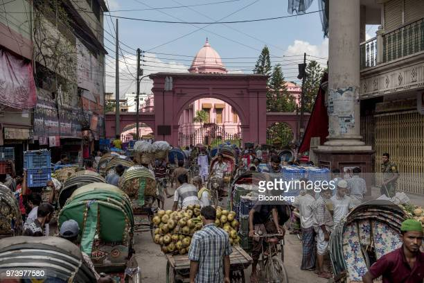 Rickshaw pullers and market vendors gather outside the Ahsan Manzil the former official residential palace and seat of the Nawab of Dhaka in Dhaka...
