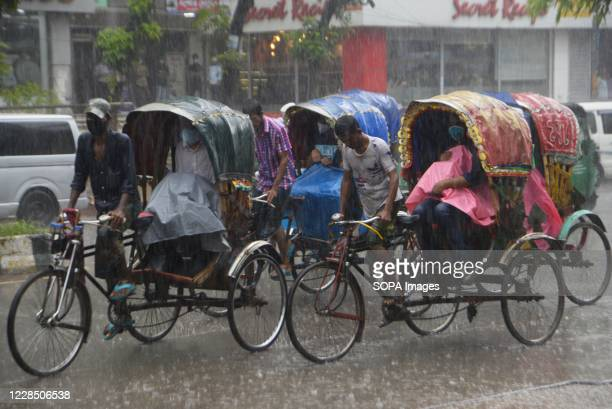 Rickshaw pullers ride on a street during heavy rainfall in Dhaka. Dhaka is getting back to its normal life after months of the ongoing Covid-19...