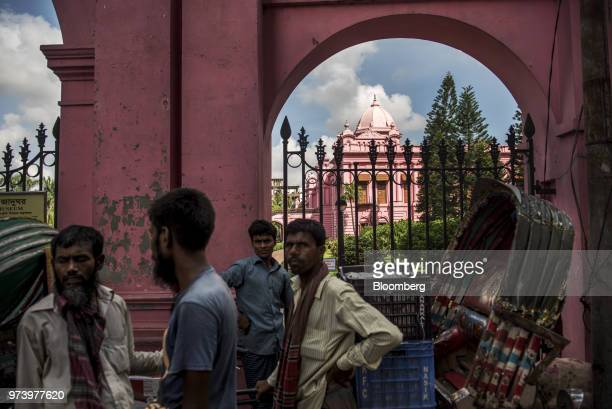 Rickshaw pullers stand outside the Ahsan Manzil the former official residential palace and seat of the Nawab of Dhaka in Dhaka Bangladesh on...